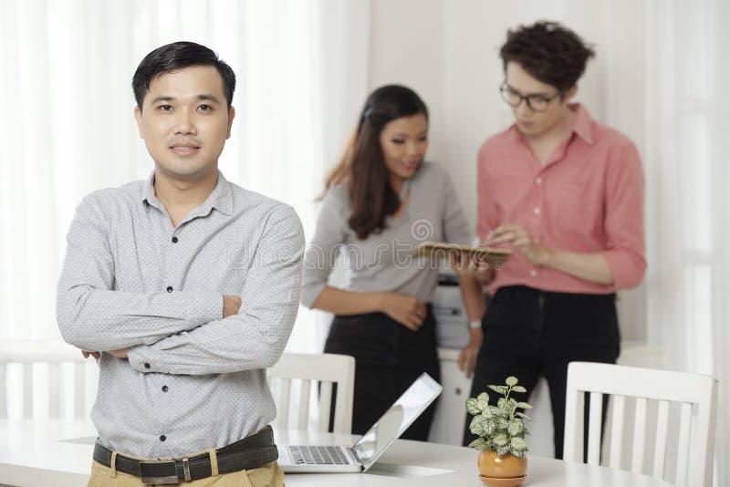 Professionele etnische arbeider met collega's in bureau royalty-vrije stock afbeelding