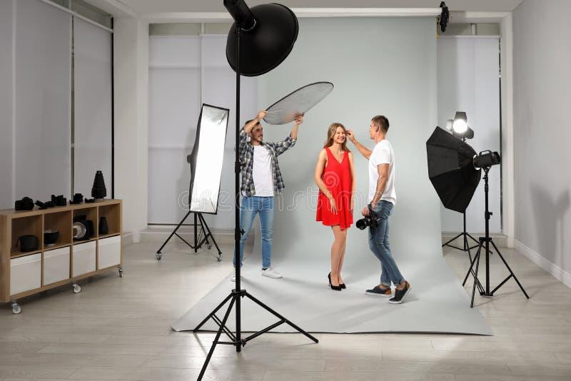 Professionele fotograaf en medewerker die met model in modern werken royalty-vrije stock fotografie