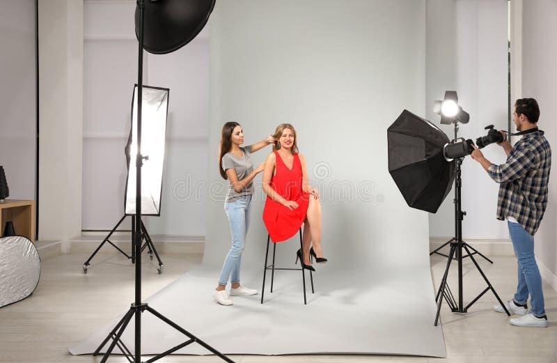 Professionele fotograaf en medewerker die met model in modern werken royalty-vrije stock foto's