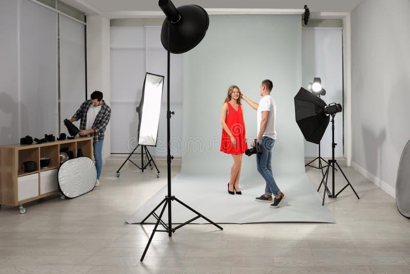 Professionele fotograaf en medewerker die met in moderne studio werken royalty-vrije stock fotografie