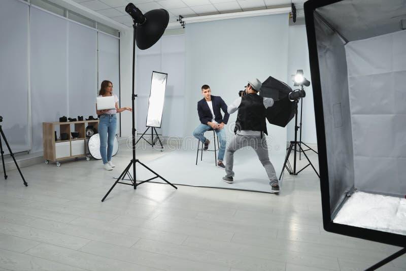 Professionele fotograaf met hulp nemend beeld van de jonge mens in modern royalty-vrije stock fotografie