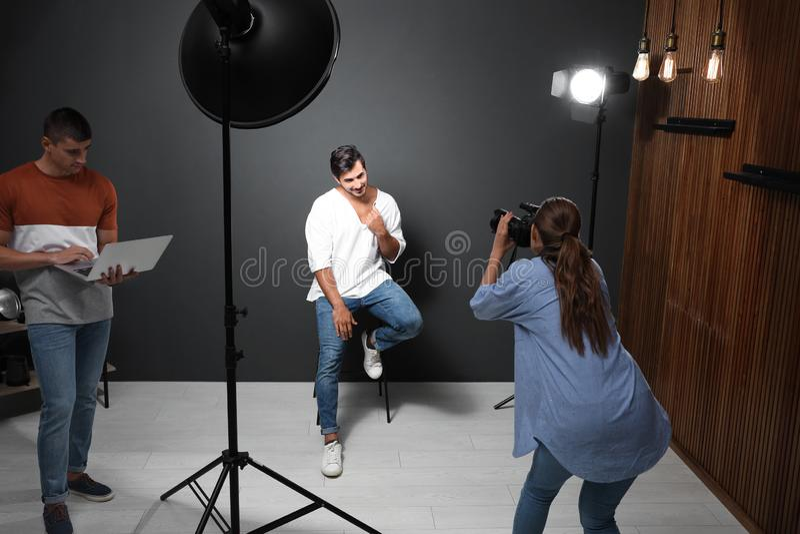 Professionele fotograaf met hulp nemend beeld van de jonge mens in modern royalty-vrije stock afbeelding
