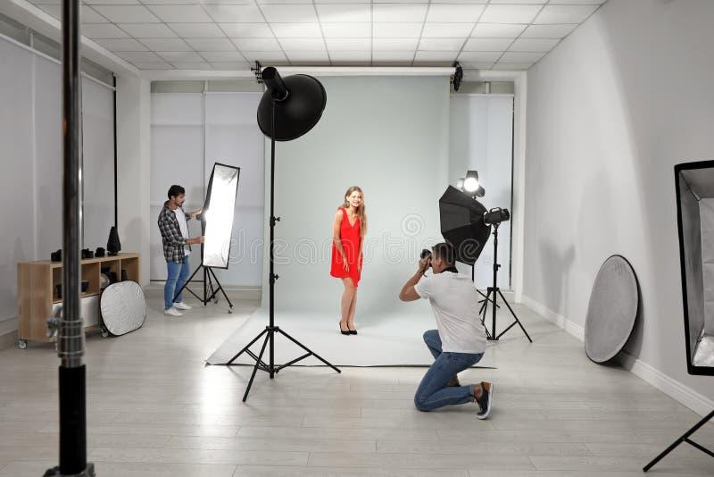 Professionele fotograaf met hulp nemend beeld van jonge vrouw in modern royalty-vrije stock foto's