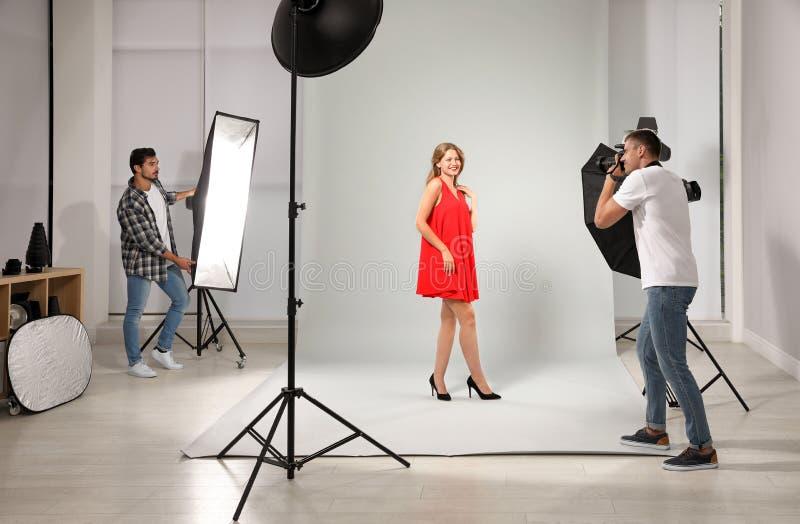 Professionele fotograaf met hulp nemend beeld van jonge vrouw stock afbeelding