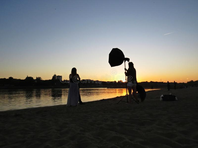 Professionele Fotograaf Photo Session met enkel Gehuwd Jonggehuwdepaar op Strand tijdens Zonsondergang stock foto