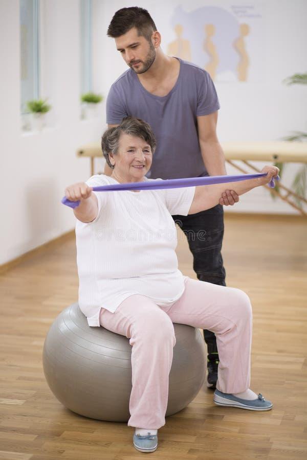 Professionele fysiotherapeut die hogere vrouwenzitting bij het uitoefenen van bal stabiliseren royalty-vrije stock foto's