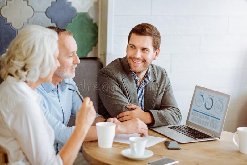 Professionele glimlachende verzekeringsmanager die met oud paar spreken stock foto's