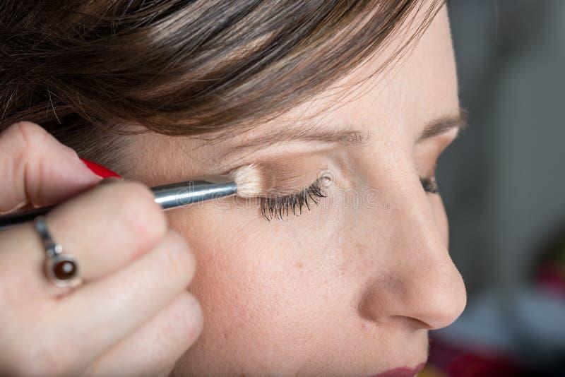 Professionele grimeur die afzonderlijke make-up toepassen stock foto