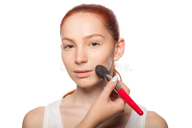 Professionele Grimeur die glamour met rode haar modelmake-up doen Geïsoleerde achtergrond royalty-vrije stock afbeelding