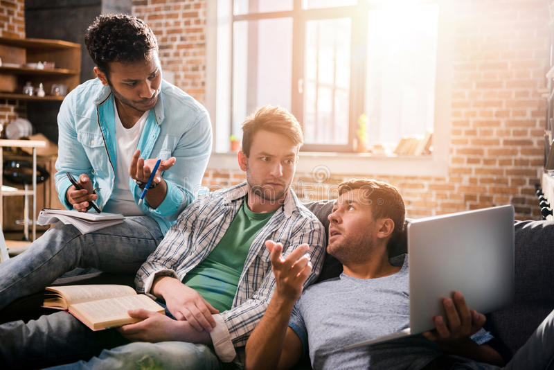 Professionele groepszitting samen op bank met laptop en het bespreken stock fotografie