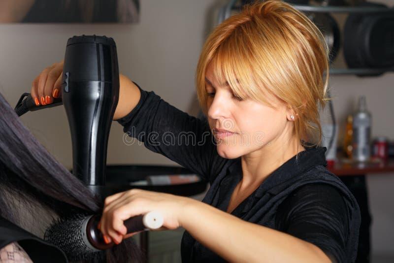 Professionele herenkapper met hairdryer en kam die bij klanten` s haar werken royalty-vrije stock fotografie
