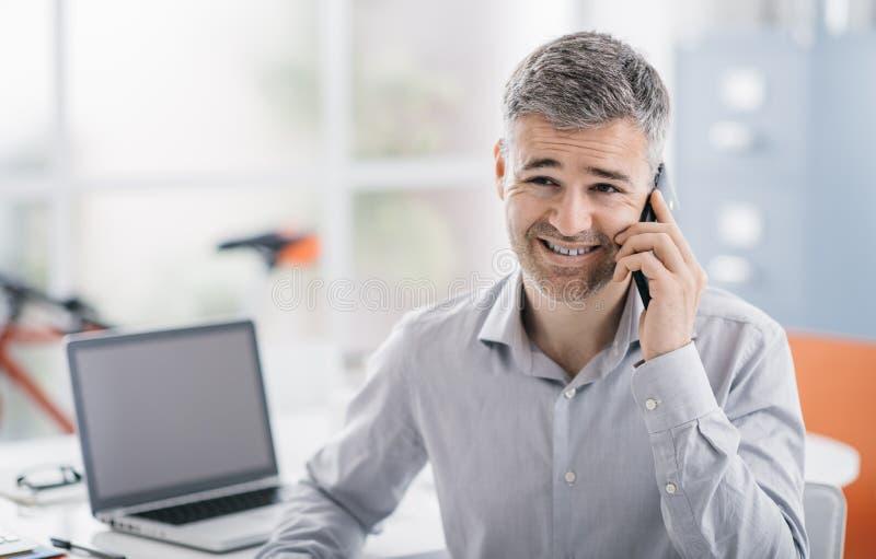 Professionele het glimlachen beambtezitting bij bureau en het hebben van een telefoongesprek met een smartphone, bedrijfs en comm stock afbeeldingen