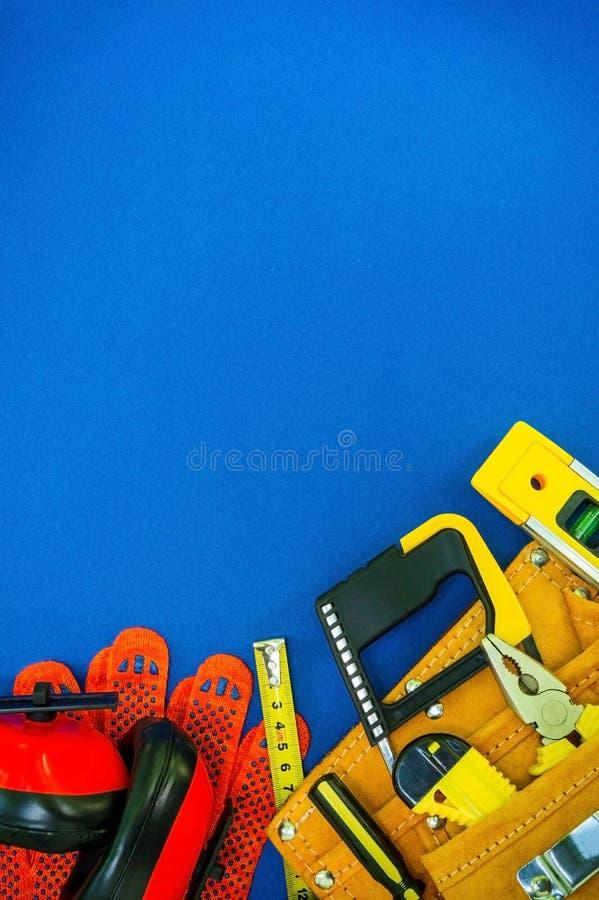 Professionele hulpmiddelen in de zak voor de schrijnwerker en vervangstukken op een blauwe achtergrond stock fotografie