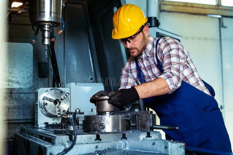 Professionele ingenieursmetaalarbeider die CNC het centrum van de malenmachine in de productie van workshop in werking stelt stock foto