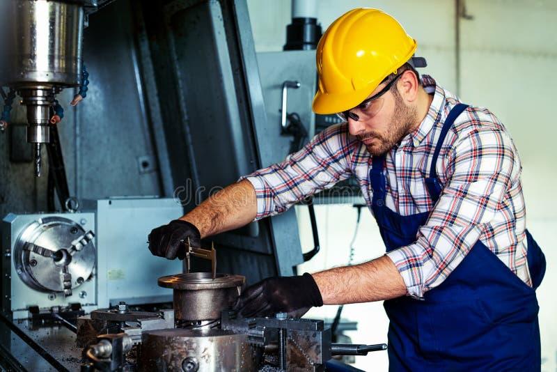 Professionele ingenieursmetaalarbeider die CNC het centrum van de malenmachine in de productie van workshop in werking stelt stock foto's