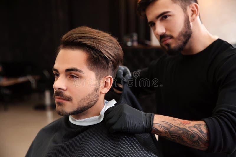 Professionele kapper die cliënt voor het scheren voorbereiden royalty-vrije stock afbeeldingen