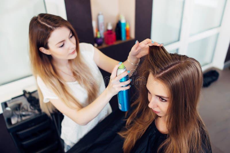 Professionele kapper die haarlak met behulp van die aan jong meisjess haar werken in schoonheidssalon royalty-vrije stock foto's
