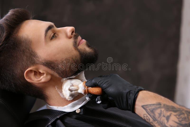 Professionele kapper die het scheren schuim op de huid van de cliënt toepassen royalty-vrije stock foto's