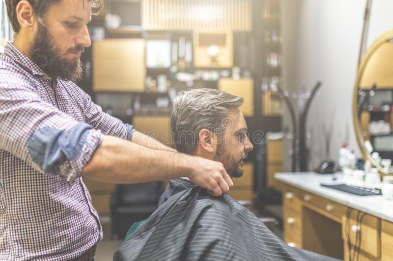 Professionele kapper klaar om en omvattend met kaap de gebaarde mens aan herenkapperachtergrond te werken royalty-vrije stock foto's