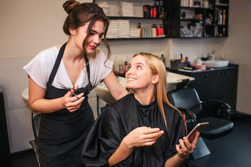 Professionele kapper met schaar en mooie vrouwelijke klant die welk te doen kapsel beslissen terwijl het bekijken telefoon stock foto