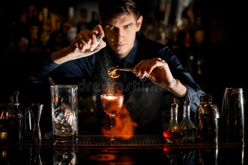 Professionele kast houdt een pincet met een stukje citrus over de sproeiers van glas vast en zet het in brand stock foto