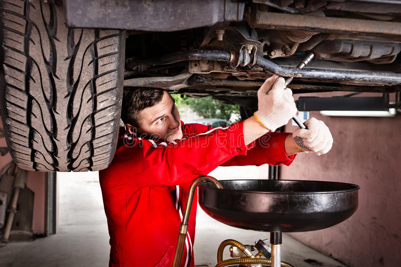 Professionele knappe mannelijke autowerktuigkundige in het eenvormige onder werken royalty-vrije stock afbeelding