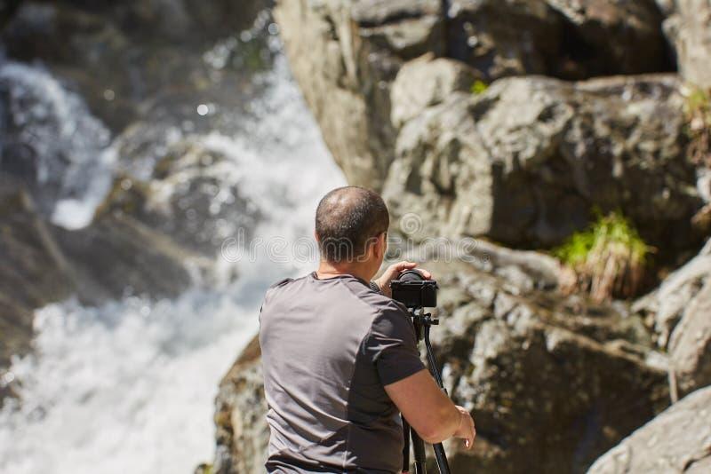 Professionele landschapsfotograaf die een waterval schieten royalty-vrije stock foto's