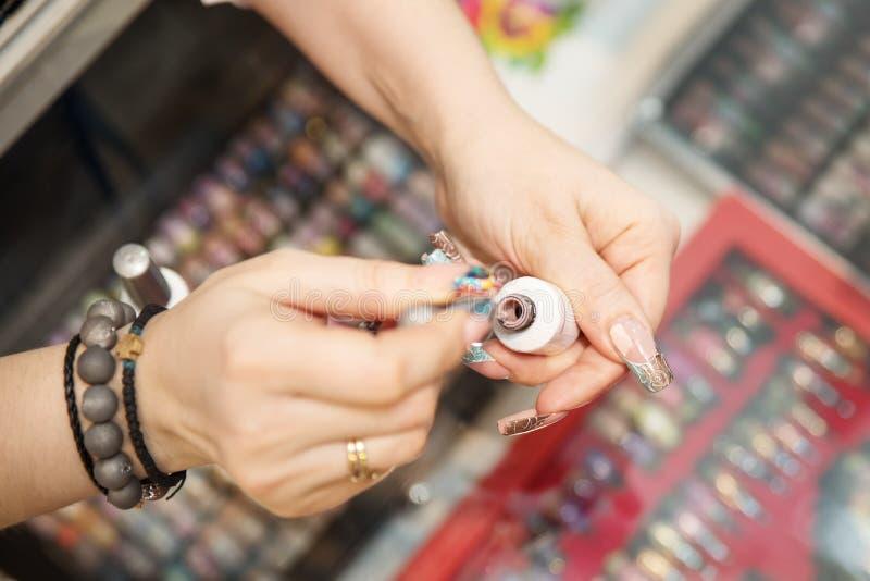 Professionele manicure die kleurrijk nagellak tonen om het afwerkingsresultaat te controleren Schoonheid en manierconcept royalty-vrije stock fotografie