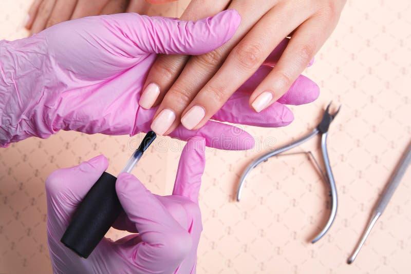 Professionele manicure die kleurrijk nagellak tonen om het afwerkingsresultaat te controleren stock afbeeldingen