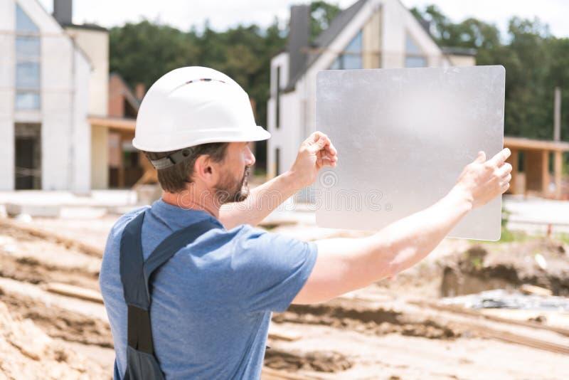 Professionele mannelijke architect die een helm dragen stock afbeelding