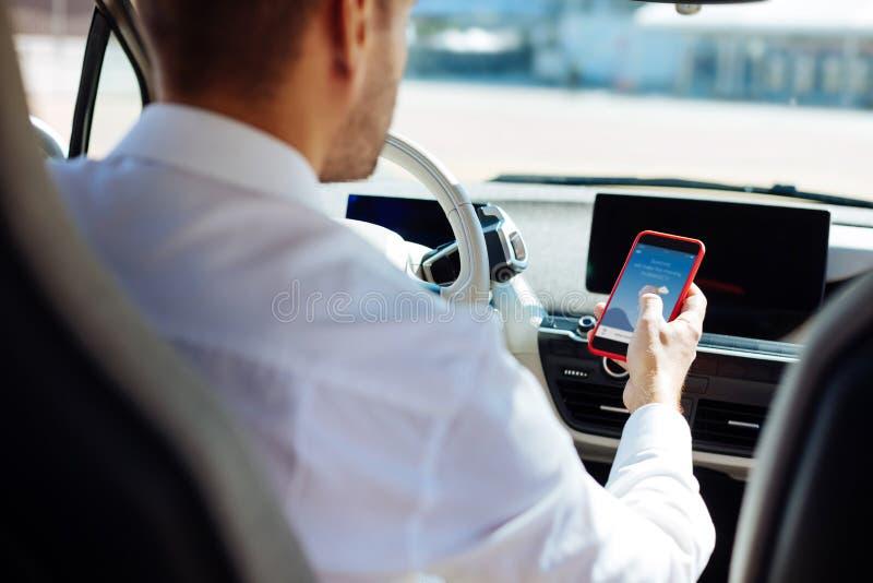 Professionele mannelijke bestuurder die zijn smartphone gebruiken stock fotografie