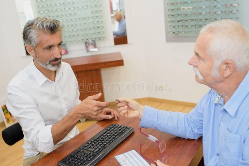 Professionele mannelijke opticien die hogere mensenklant raadplegen stock foto