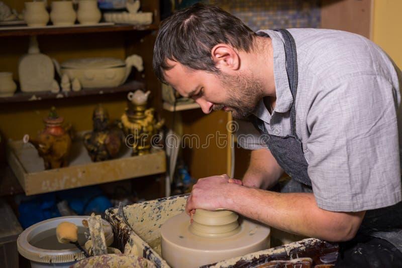 Professionele mannelijke pottenbakker die met klei aan pottenbakkers` s wiel werken royalty-vrije stock foto's
