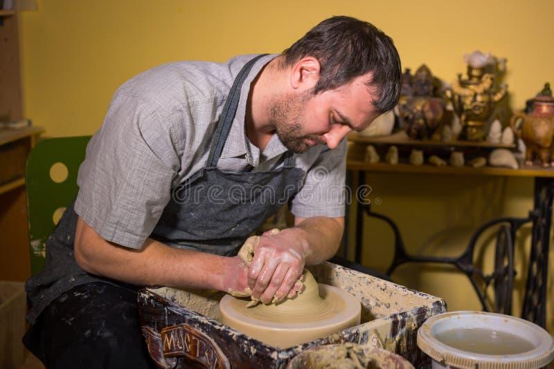 Professionele mannelijke pottenbakker die met klei aan pottenbakkers` s wiel werken royalty-vrije stock foto