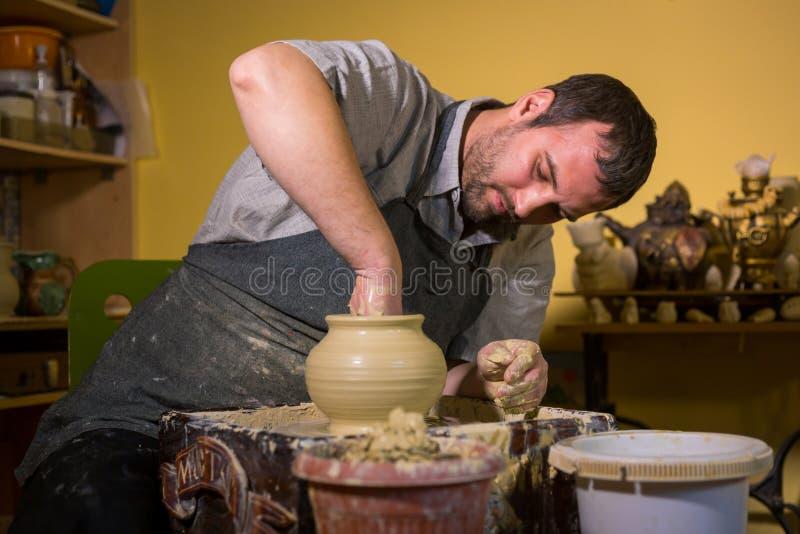 Professionele mannelijke pottenbakker die met klei aan pottenbakkers` s wiel werken royalty-vrije stock afbeeldingen