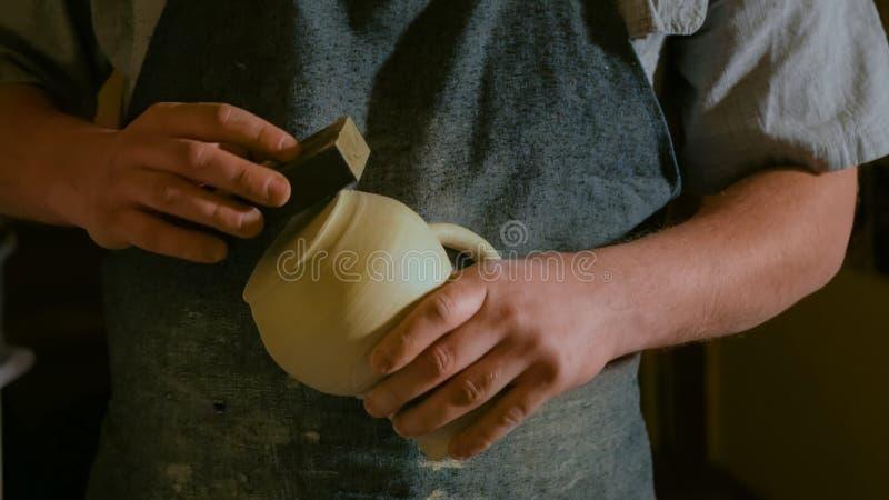 Professionele mannelijke pottenbakker die in workshop werken stock afbeelding