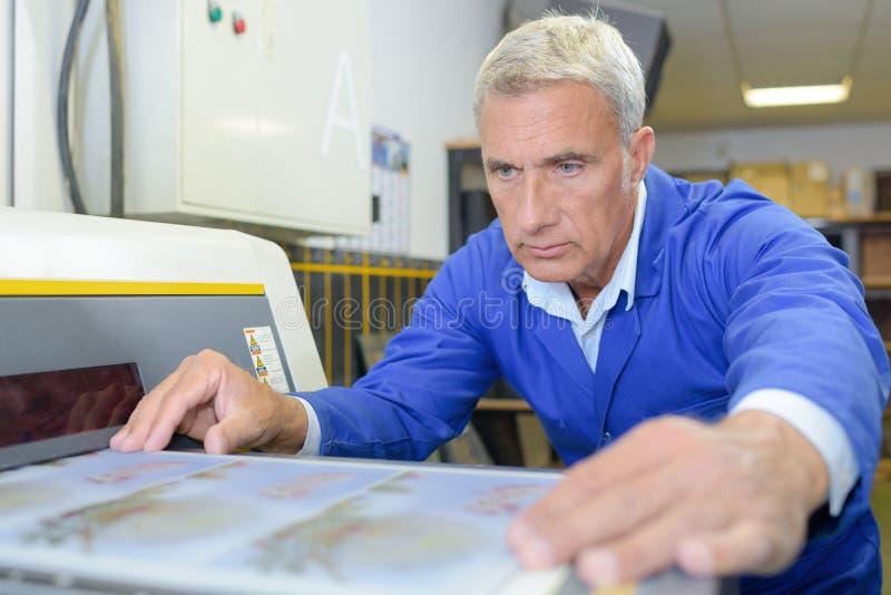 Professionele mens die aan druksysteem werken stock afbeeldingen