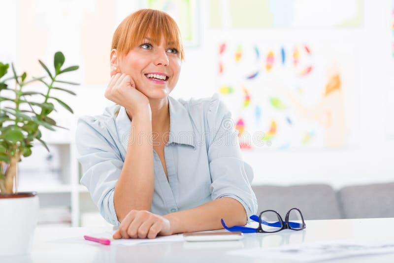 Professionele mooie jonge vrouw die haar bureau zitten bij haar huis stock afbeeldingen