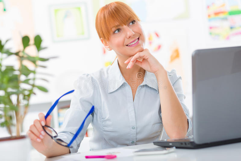 Professionele mooie jonge vrouw die haar bureau zitten een holdingsglazen in haar handen stock fotografie