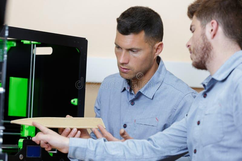 Professionele ontwerper en student die zich naast 3d printer bevinden royalty-vrije stock foto