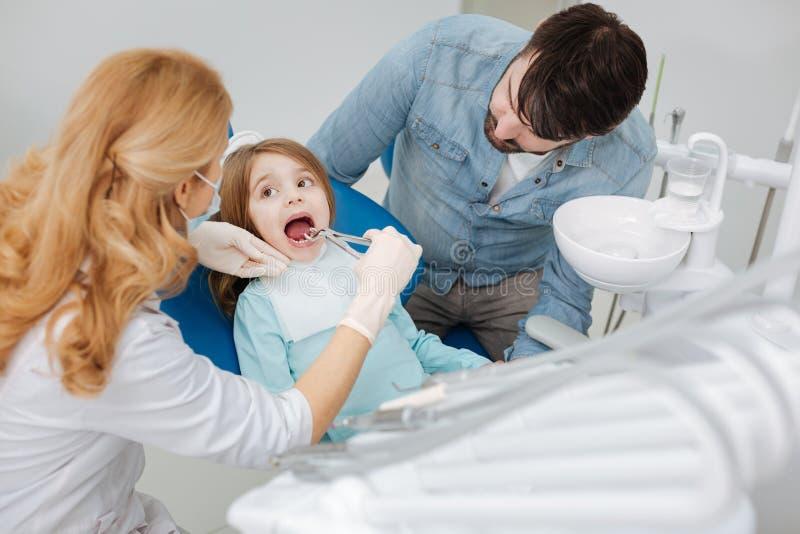 Professionele pediatrische tandarts die zeer aandachtig zijn royalty-vrije stock foto's