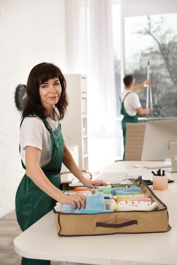 Professionele portier met organisator en schoonmakende levering in bureau royalty-vrije stock afbeelding
