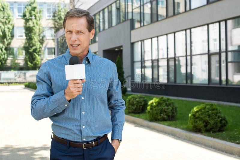 professionele rijpe nieuwsverslaggever die met microfoon spreken royalty-vrije stock afbeelding