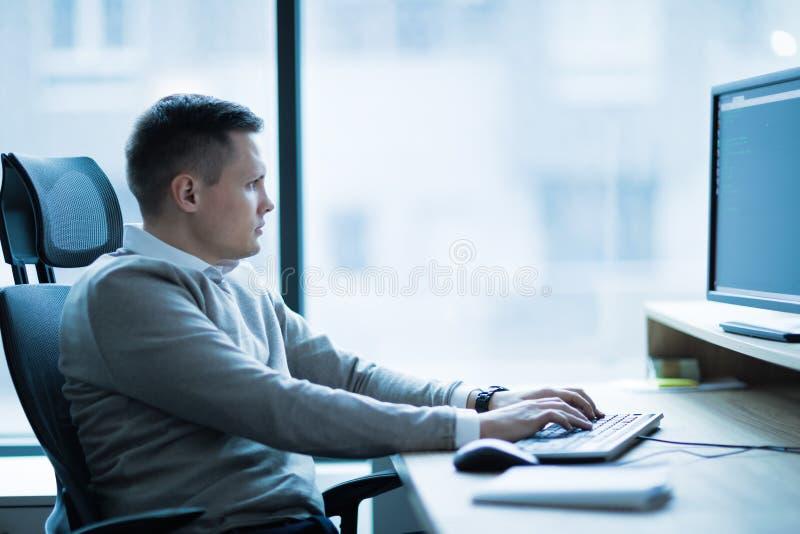 Professionele softwareontwikkelaar die in bureau werken stock foto