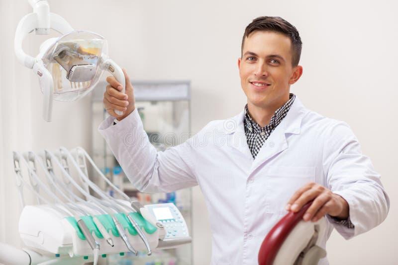 Professionele tandarts die bij zijn tandkliniek werken stock foto's