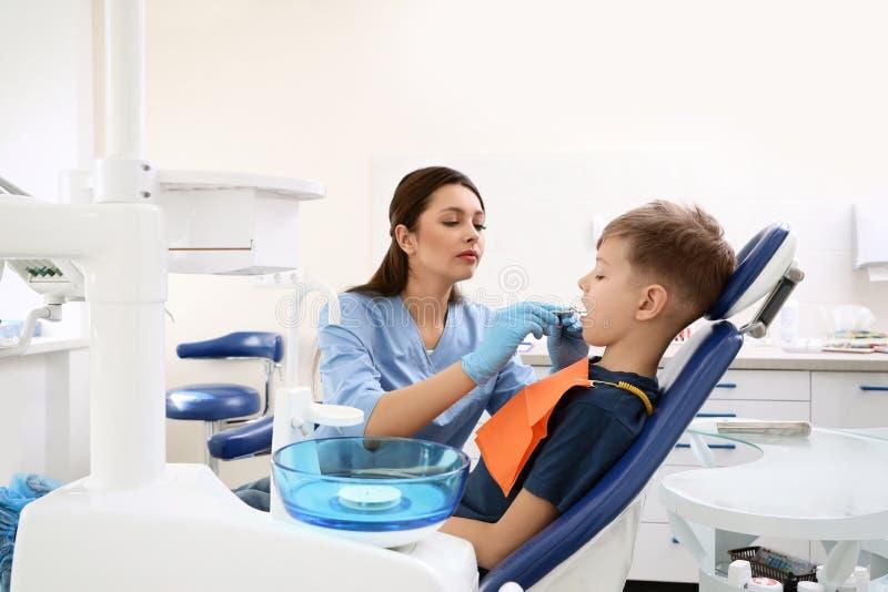 Professionele tandarts die met weinig jongen werken stock afbeelding