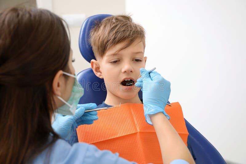 Professionele tandarts die met weinig jongen werken royalty-vrije stock afbeelding