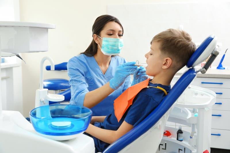 Professionele tandarts die met weinig jongen werken stock afbeeldingen