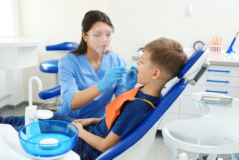 Professionele tandarts die met weinig jongen werken royalty-vrije stock afbeeldingen