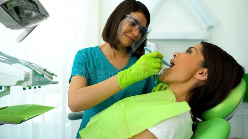 Professionele tandarts die vrouwelijke geduldige tanden, regelmatige controle in kliniek onderzoeken stock afbeeldingen